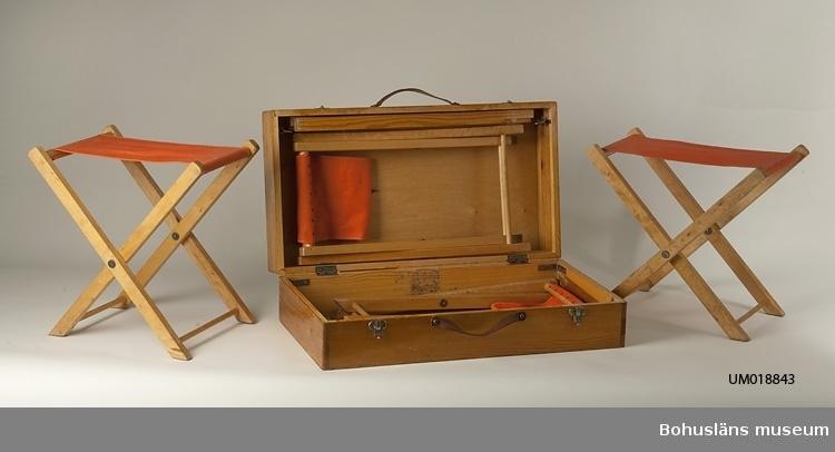Låda för campingstolar UM 18844:1-4. Lackat trä och läderhandtag. Metallås, två st. Fäller man ut ben ur lådan blir det ett bord. Inköpt på Uddevalla Tennisklubbs loppmarknad för 30:-.