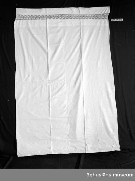 """782 Förv från *3 MARIESTAD 471 Tillverkningstid 1930-1932 410 Mått/Vikt !L:205 B:135 CM 601 Vitt. Gjort av en säck. Virkad spets och korsstygnsbroderi (""""AP"""") 602 utförd av stenhuggarehustrun Astrid Pettersson, Örn, Sotenäs."""