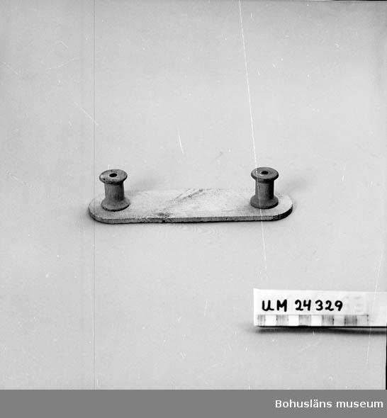 782 Förv från *NLYCKE 410 Mått/Vikt !L:21 B:6 CM 594 Landskap BOHUSLÄN 601 Två tomma trådrullar fastspikade på en träplatta med runda kortsidor.
