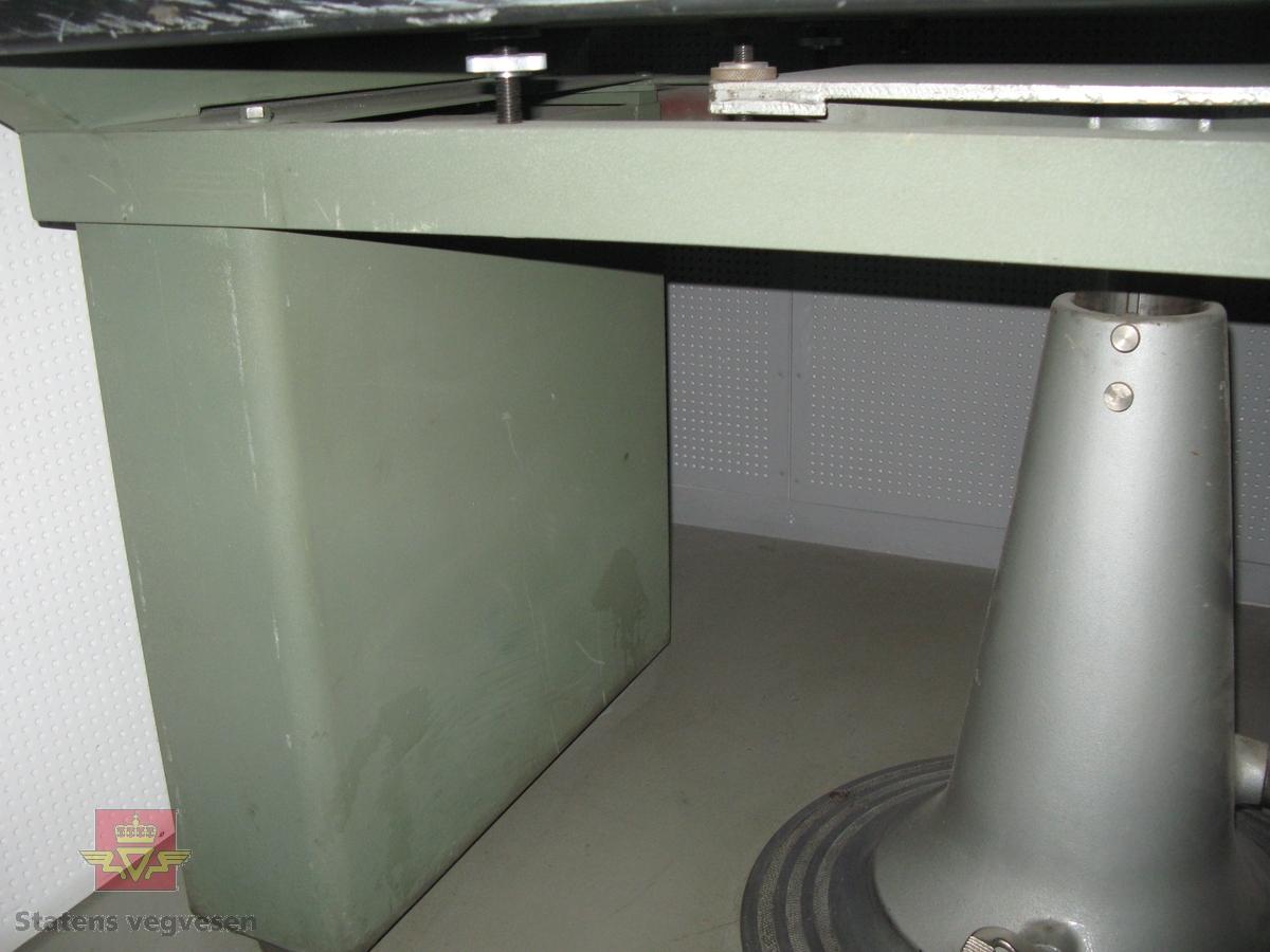Grønn plotter med tre prosjektorer. Svart hev og senk bord på en søyle. En-fas 220 volt strømkabel. Merking fra produsent.