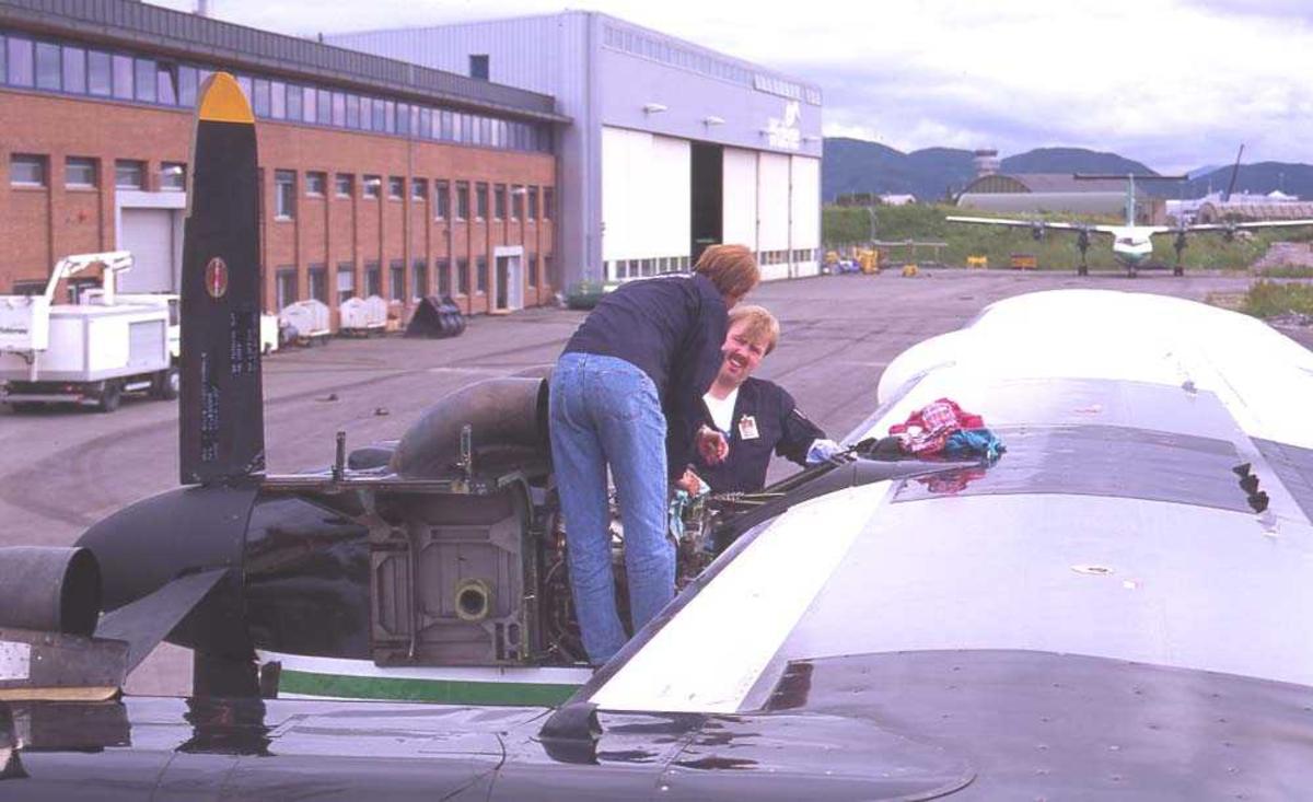 Lufthavn/flyplass. Bodø. Widerøes hangar. To personer. Ett fly, LN-WFE, DHC-7-102/ Dash7 fra Widerøe parkert. Flyteknikere inspiserer og tar vedlikehold.