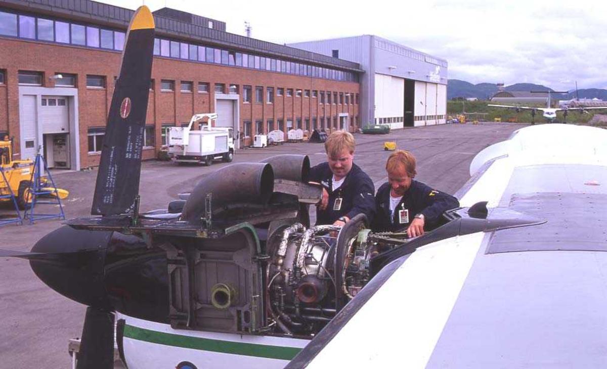 Lufthavn/flyplass. Bodø. Widerøes anlegg Langstranda. To personer. Ett fly, LN-WFE, DHC-7-102/ Dash7 under vedlikeholdsarbeid.
