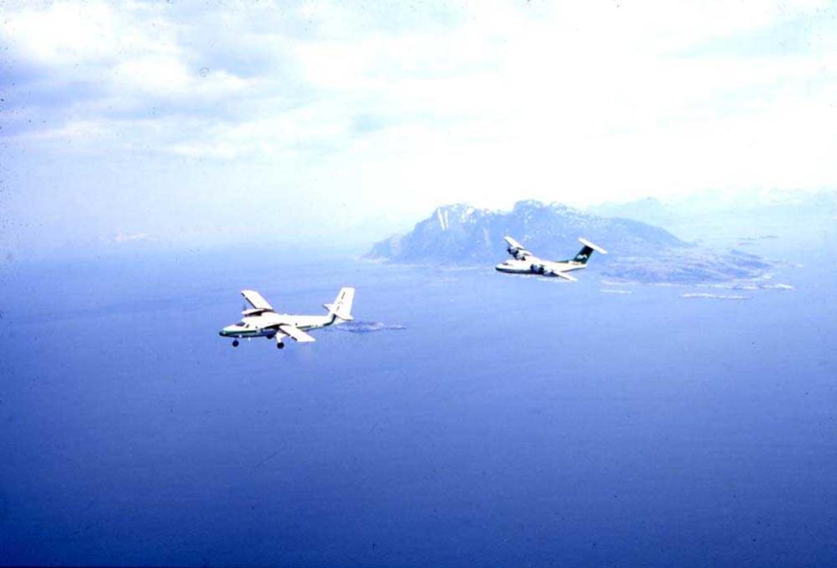Luftfoto. To fly, LN-WFG, DHC-7-102 Dash7 og LN-BNM, DHC-6-300 Twin Otter fra Widerøe passerer sørenden av Landegode som ses i bakgrunnen.