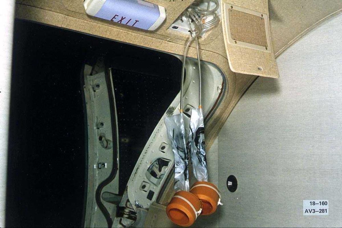 En oksygenmaske som henger ned fra en luke, foran en dør, på en Boeing 737-200.