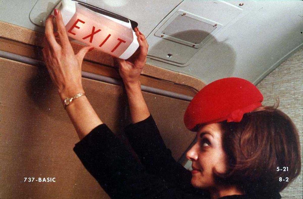 En person som setter opp/tar ned et exit-skilt over en dør på ett fly, Boeing 737-200.