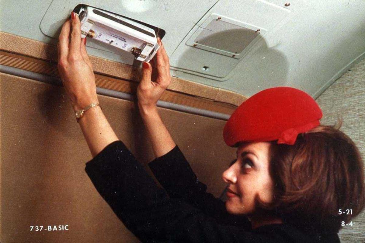 En person setter opp/tar ned et exit-skilt over en dør i ett fly, Boeing 737-200.