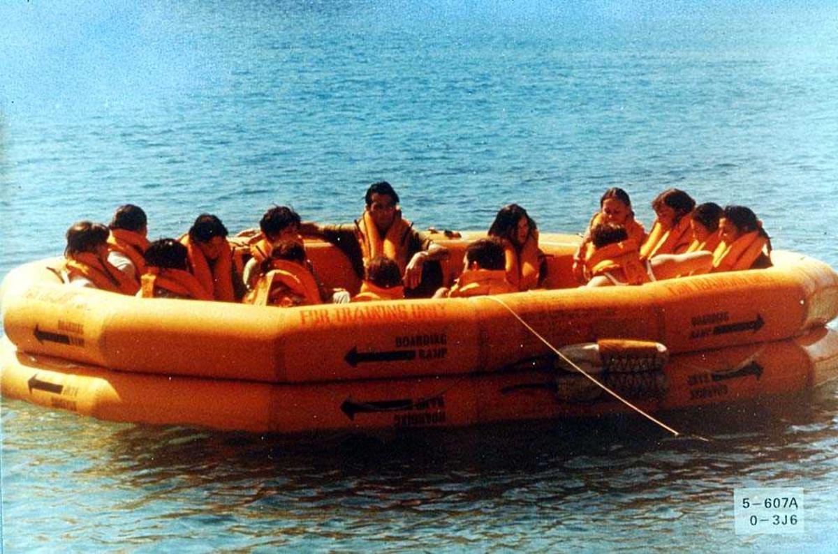 Flere personer som sitter ombord i en redningsflåte på vannet, for bruk i et fly.