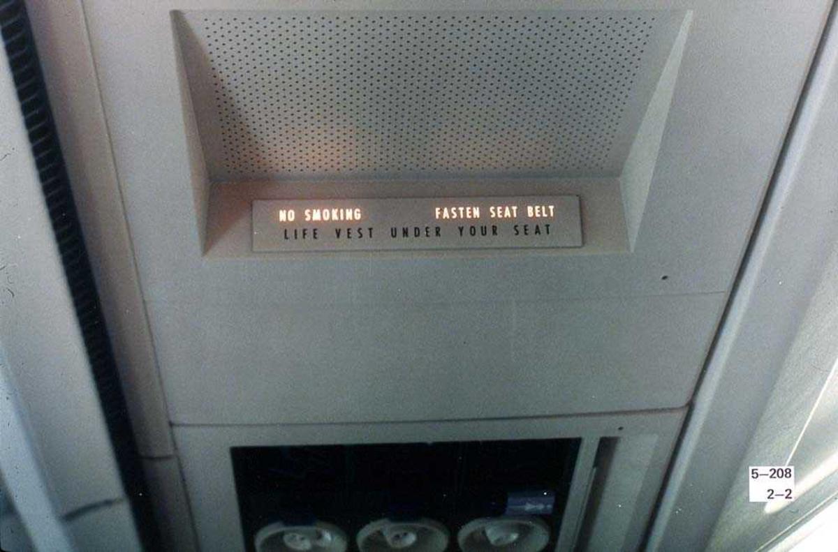"""Detaljbilde av et informasjonsskilt ombord i ett fly, Boeing 737, som viser """"No smoking"""" og """"Fasten seat belt""""."""