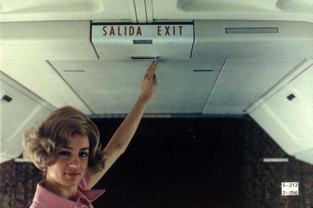 En person inne i ett fly, Boeing 737-200, som peker på et exit-skilt.