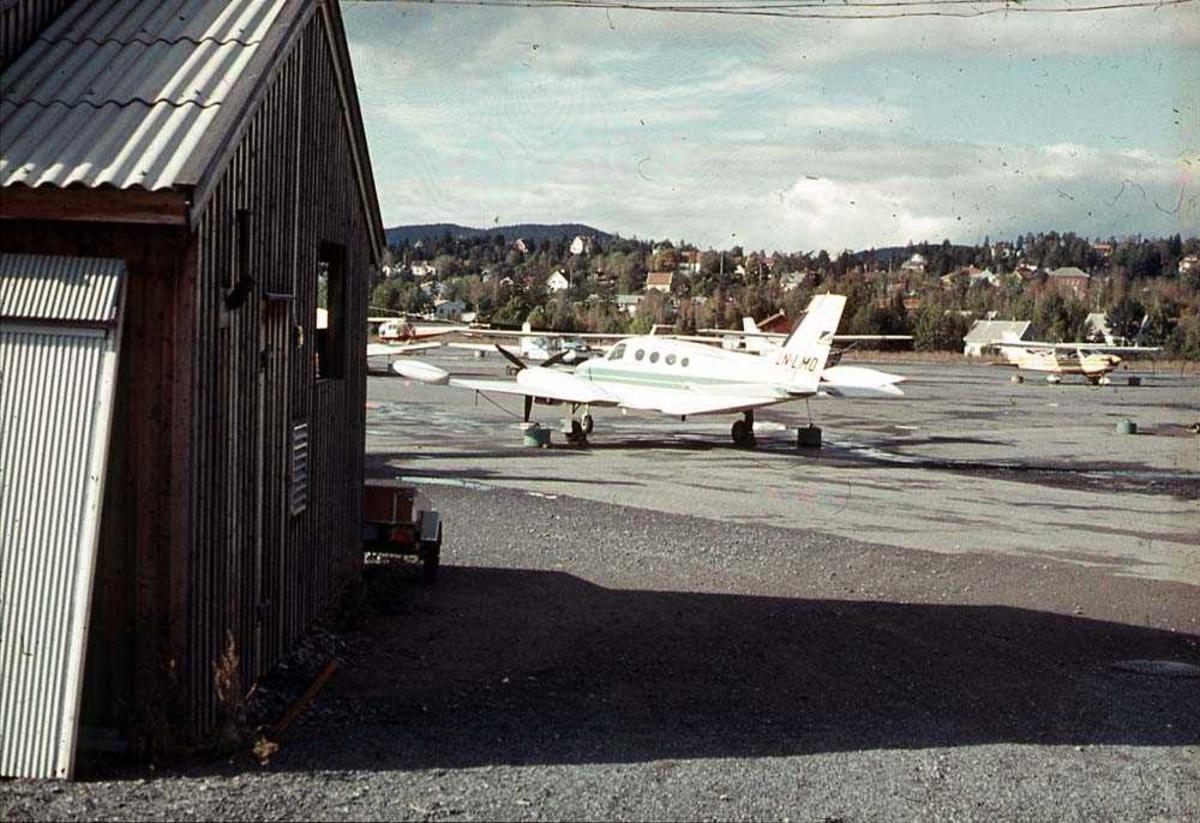 Lufthavn. Ett fly på bakken, Cessna 401A LN-LMO fra Widerøes Flyveselskap. Flere andre fly og bygninger i bakgrunnen. Bygning i forgrunnen.