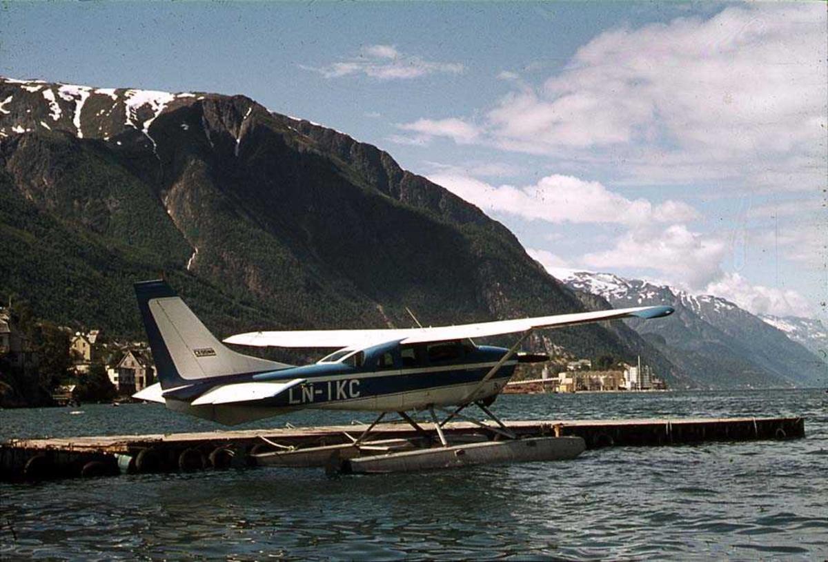 Ett fly på vannet ved en brygge, Cessna 206C LN-IKC. Fjell i bakgrunnen.