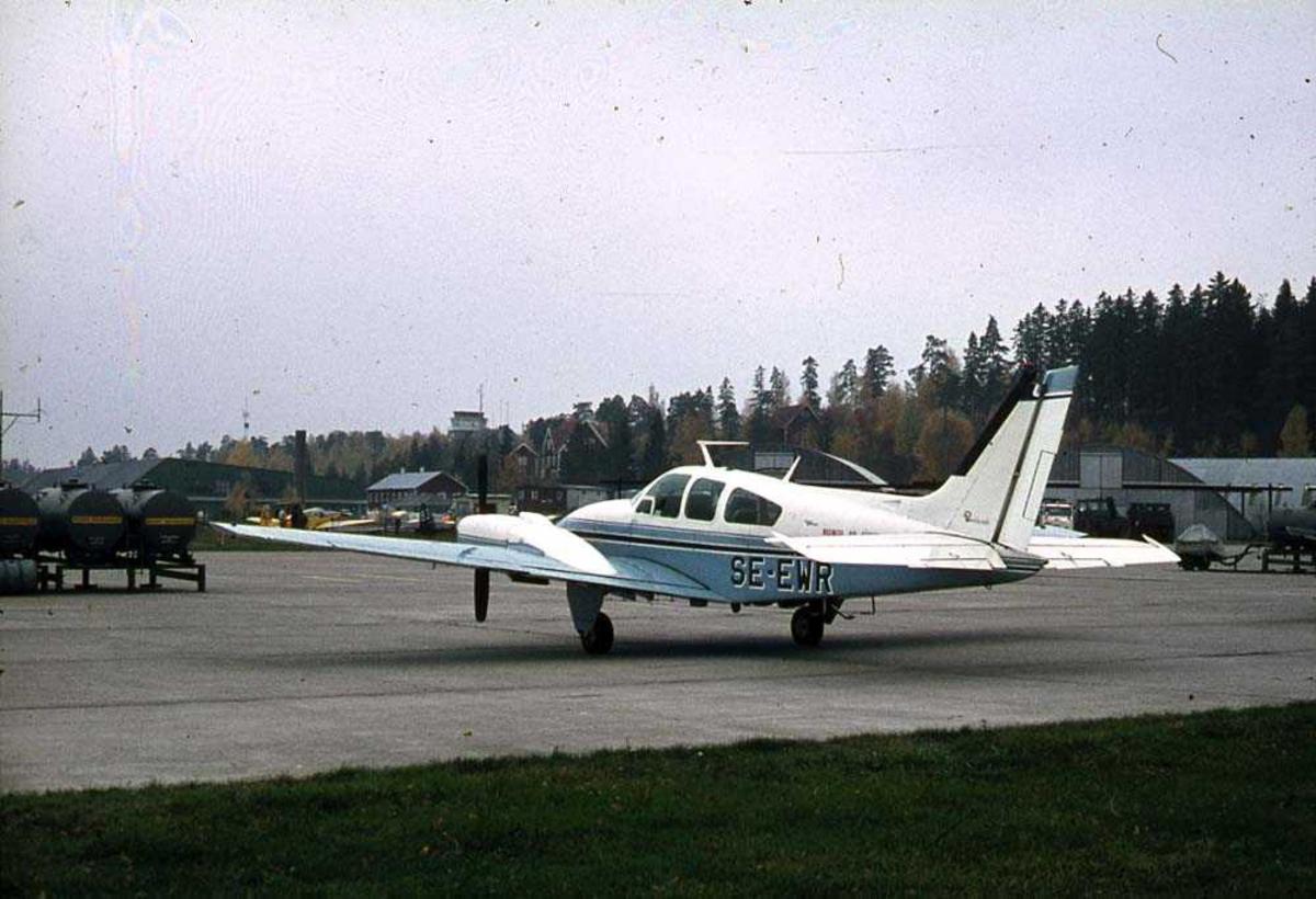 Lufthavn. Ett fly på bakken, Beechcraft 95-B55/C55 Baron SE-EWR. Bygninger i bakgrunnen.
