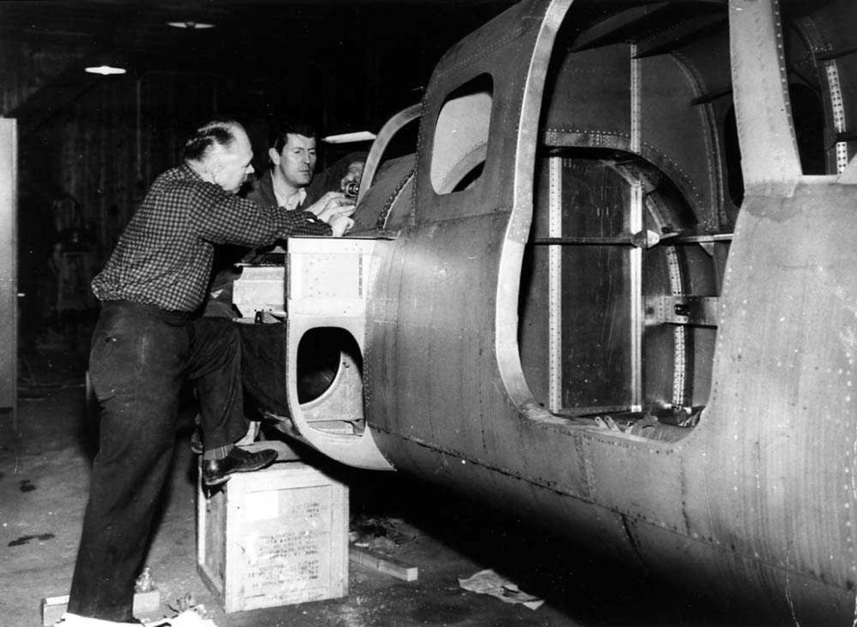 To personer som bygger på ett fly, C. L. Larsens jet-trainer.