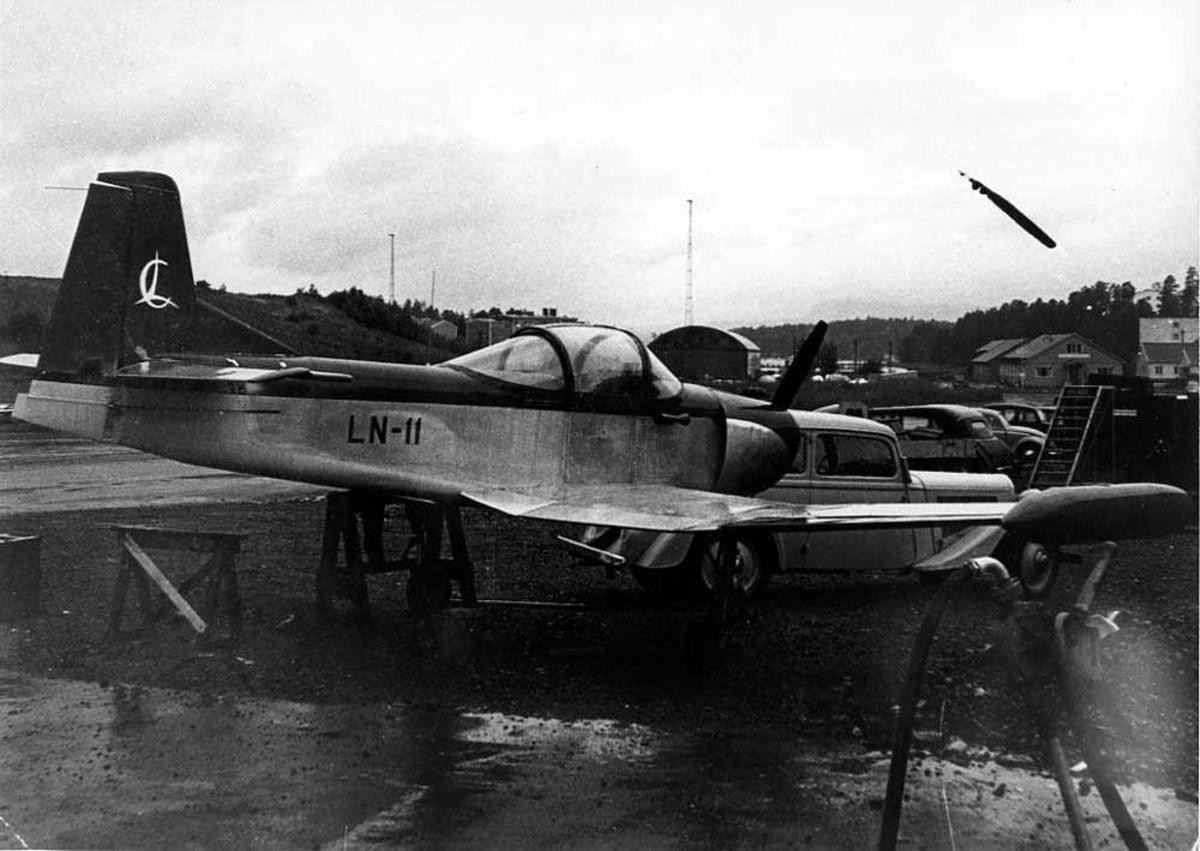 Ett fly på bakken, Larsen Spesial LN-11. Flere kjøretøy og bygninger i bakgrunnen.
