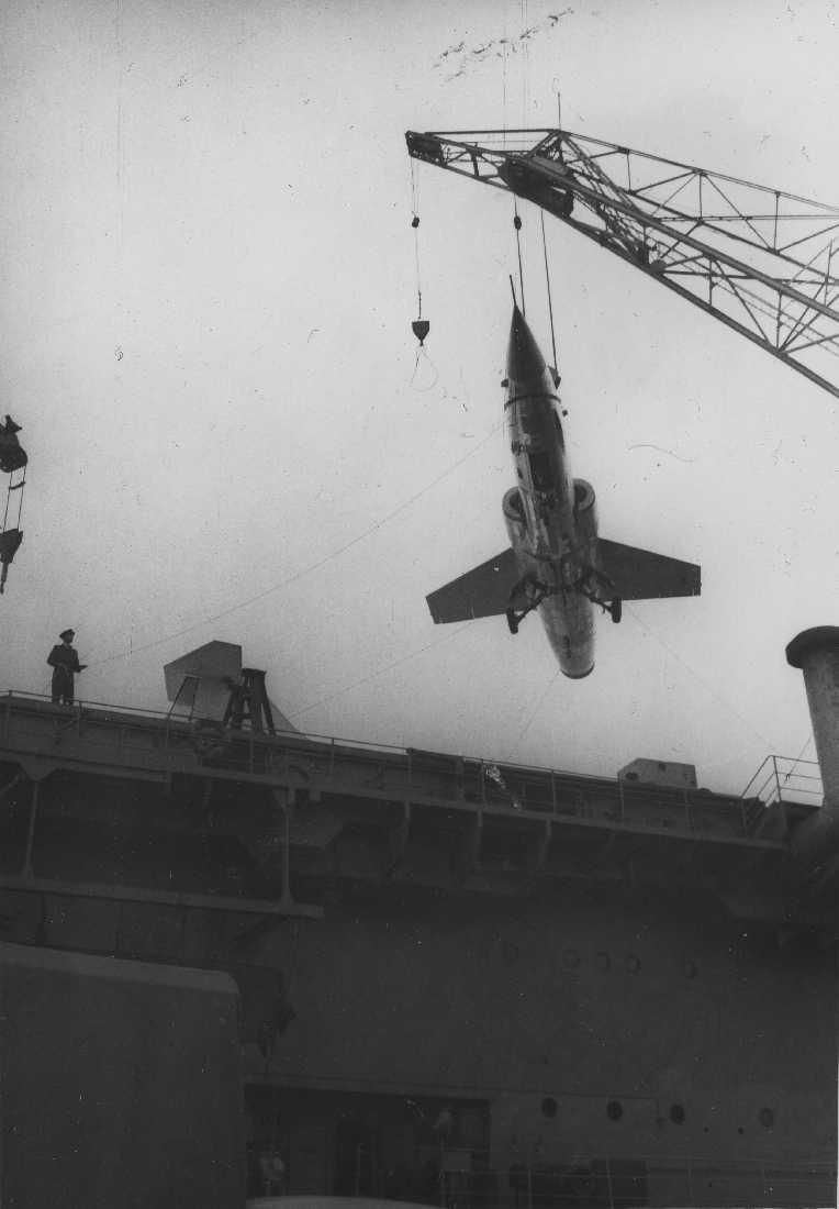 Båt - Marinefartøy. Ett fly, F-104 Starfighter henger i en heisekran. Flyet heises fra et fartøy