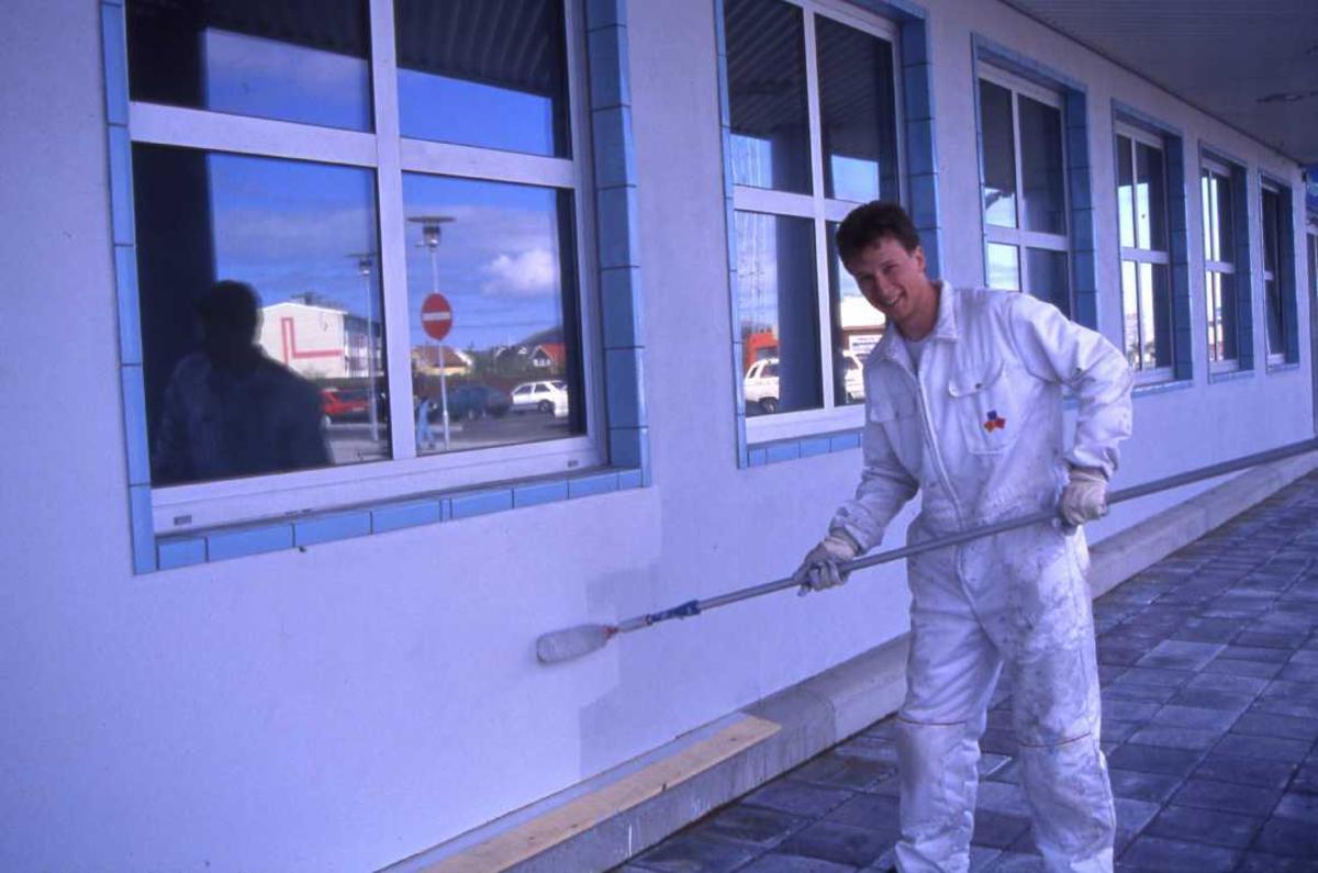 Lufthavn - flyplass. Bodø nye Lufthavn. En person maler fasaden på nybygget.