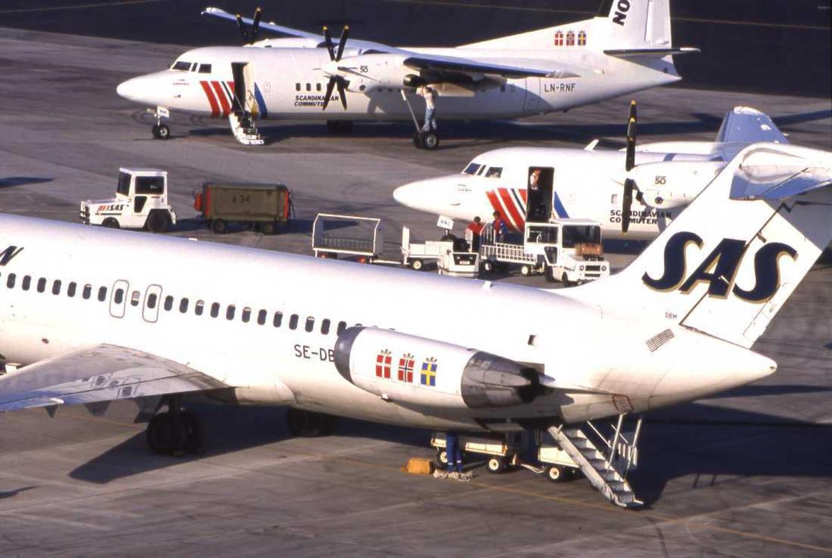 Lufthavn - flyplass. Bodø nye Lufthavn. Et knippe med SAS-fly står parkert ved den gamle flyterminalen. En DC-9 og to Fokker 50..