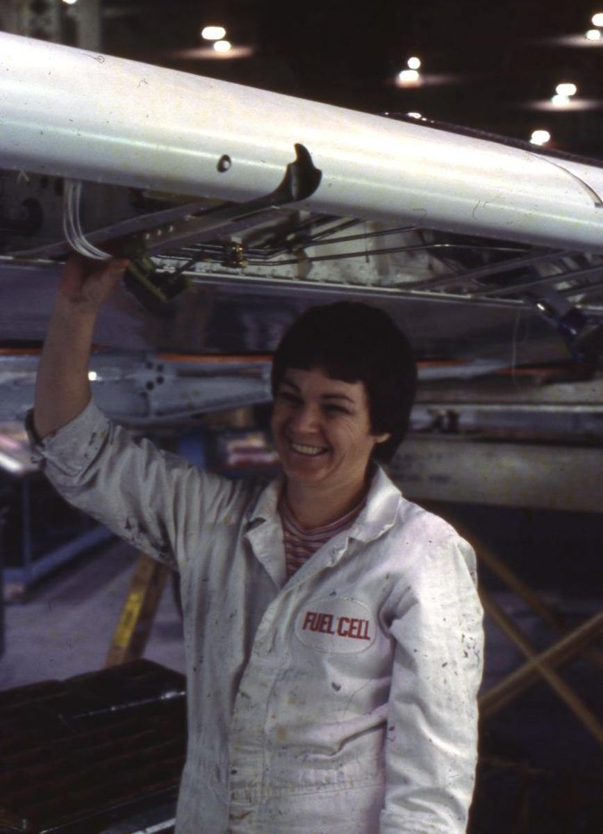 Landskap. Boeings flyfabrikk Seattle. En person (flytekniker) under en blottlagt vinge med drivstoff koblinger..