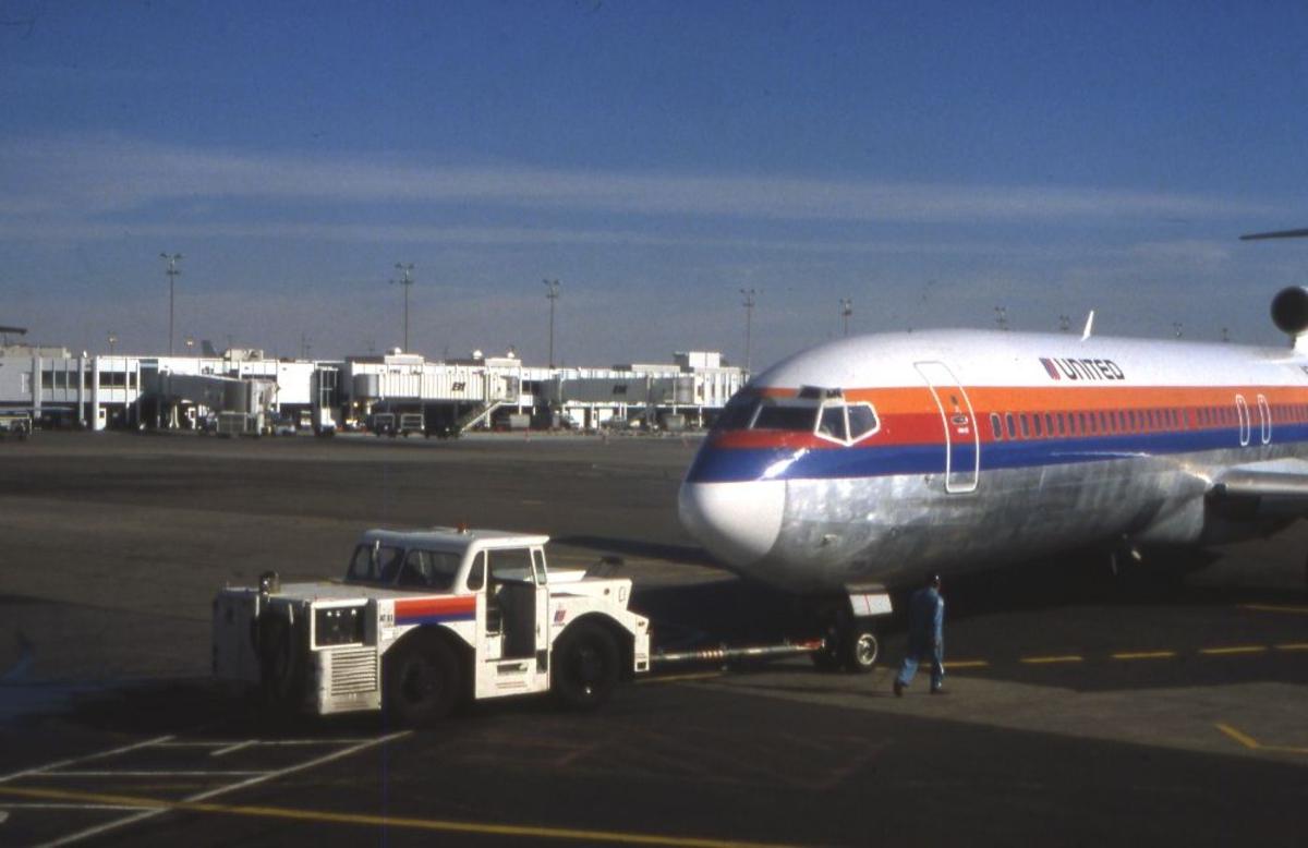 Lufthavn/Flyplass. Et fly fra flyselskapet United, USA, trekkes ut fra oppstillingsplass av en truck.