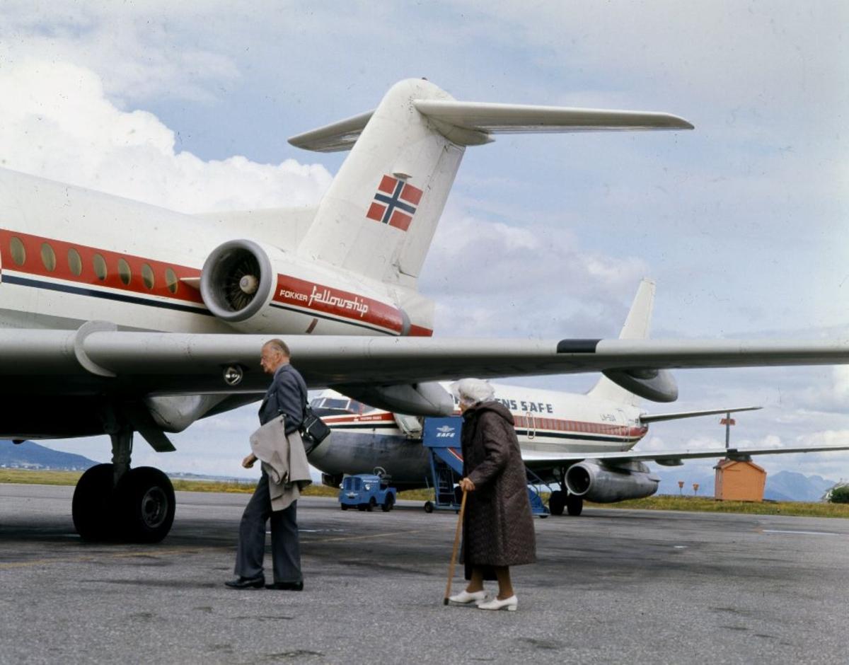 Lufthavn/Flyplass. To fly parkert, en Fokker F-28 Fellowship og i bakgrunn en Boeing 737, fra Braathens SAFE. To passasjerer går ombord.