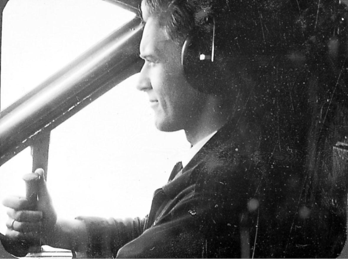 Portrett. 1 person, flyger, sitter i cockpiten på et fly.