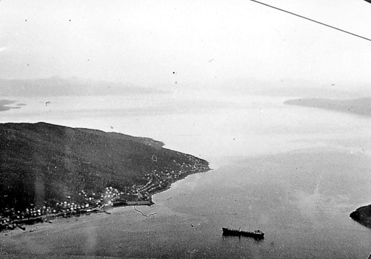 Luftfoto.  Land og hav under. 1 båt og noe spredt bebyggelse. Tatt fra fly.