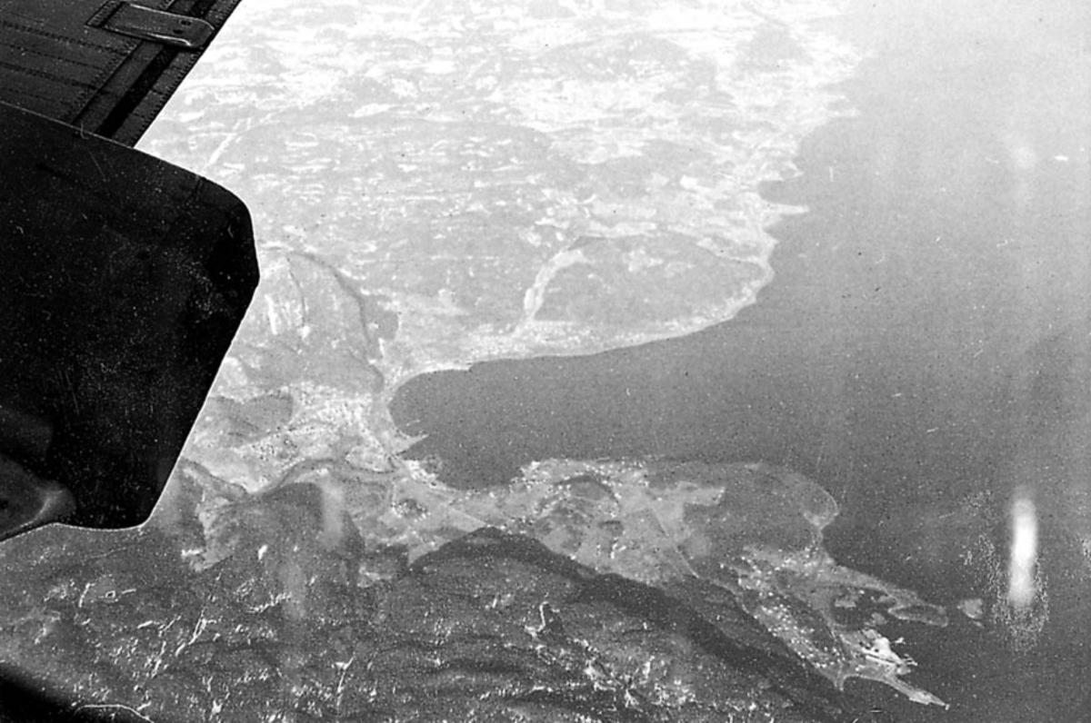 Luftfoto tatt fra fly, litt av vingen på flyet sees. Land med bebyggelse og hav under.