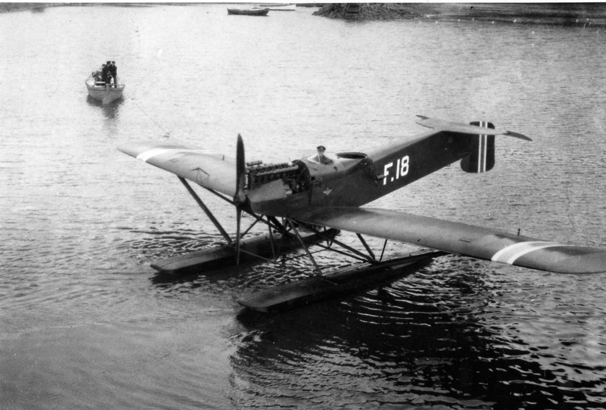 Ett fly, Hansa Brandenburger Nr. 64-F18.  en person i cockpit. Noen personer i en båt lenger bak.
