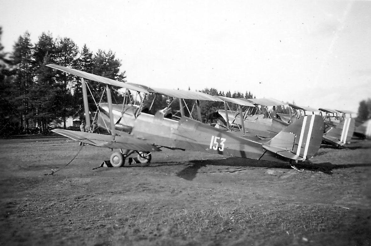 Åpen plass, ant. lufthavn. Flere fly på bakken, fremst, DH 82A Tiger Moth. Nr. 153. Andre fly bak.