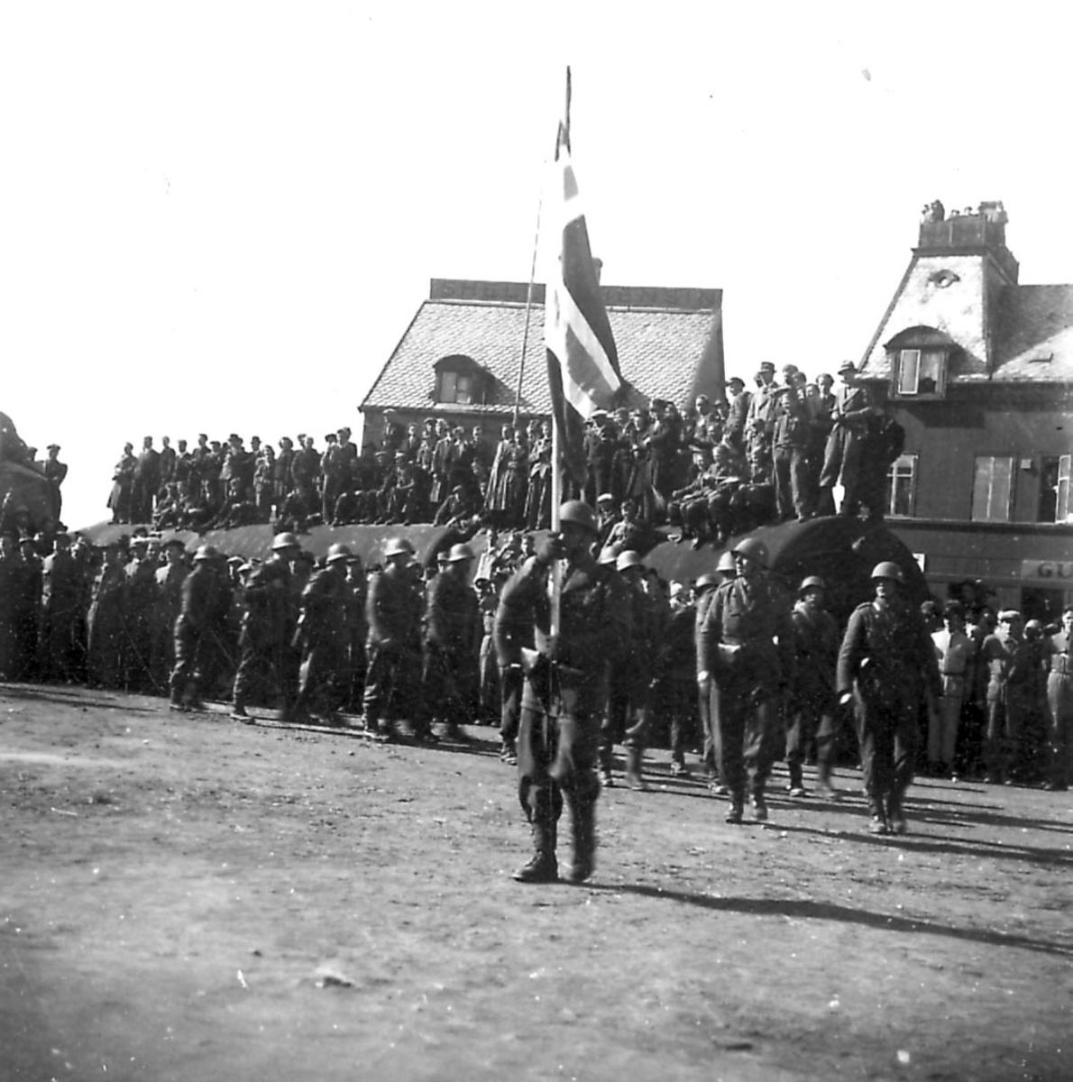 """Frigjøringsdagene i Bodø etter krigen 1940 - 1945. Fra kaiområdet, stor sylinderformet """"tank"""" foran noen bygninger. Mange personer samlet på tanken. En gruppe soldater oppstilt foran."""