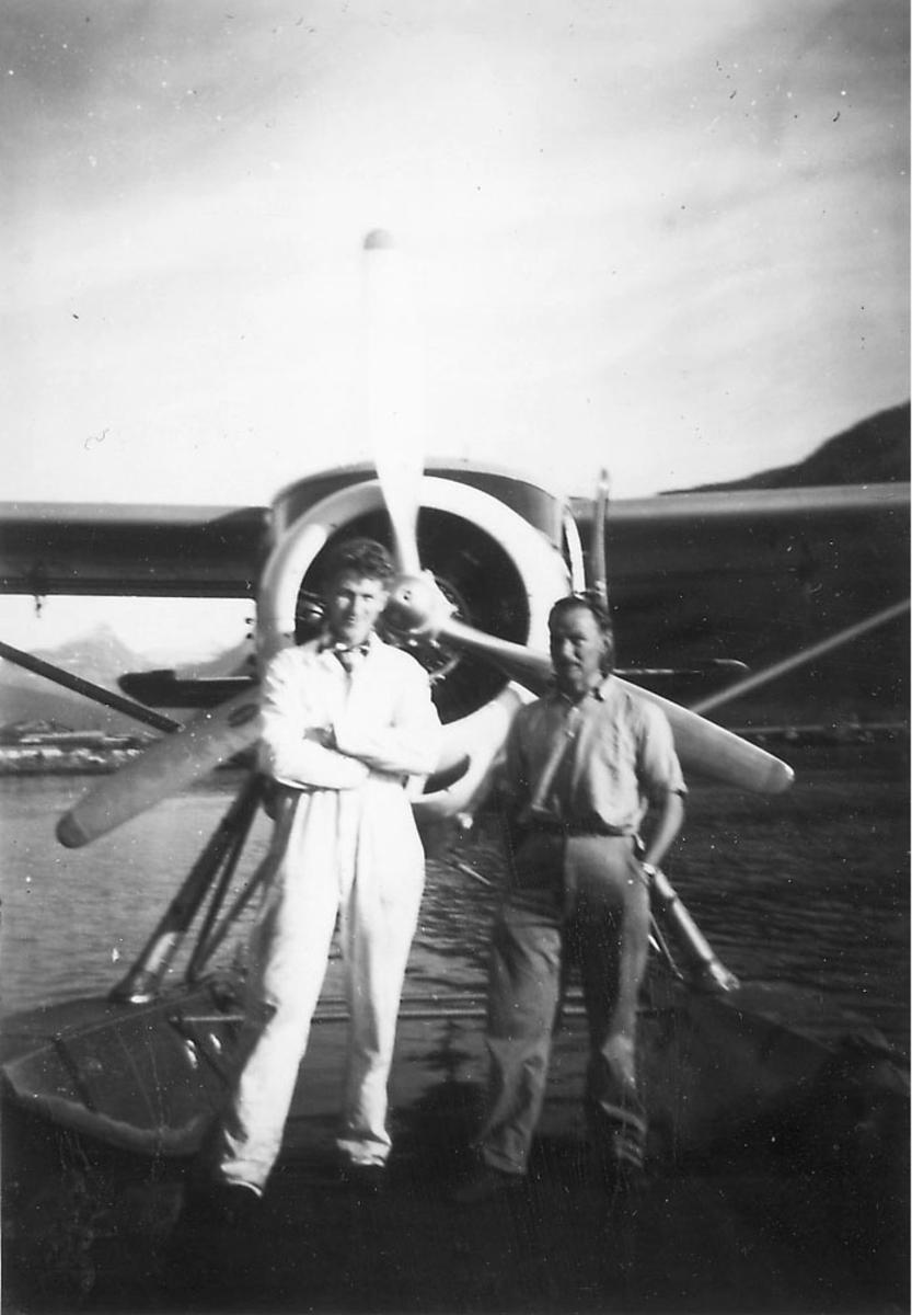 Sjøflyhavn, ett fly i vannkanten, Otter, fortøyd ved en brygge. To personer står foran flyet.