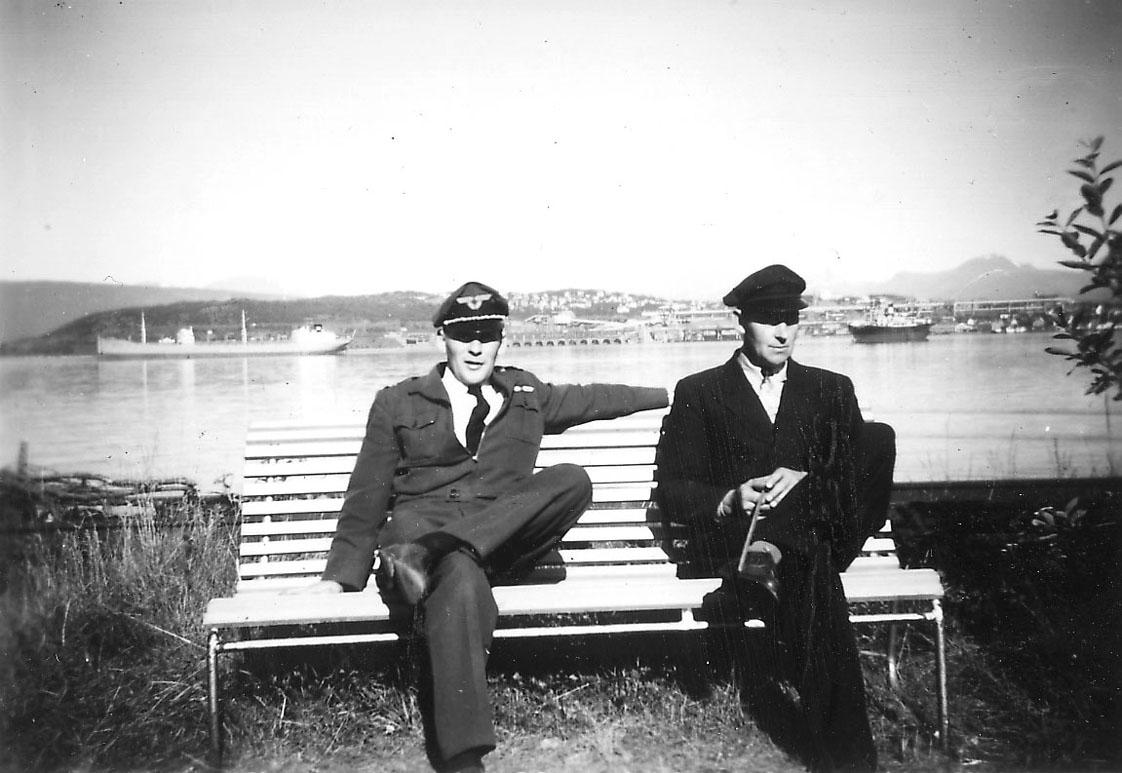 Portrett, to personer på en benk i forgrunnen. Havneområde bak med bl.a. to større båter (malmbåter).