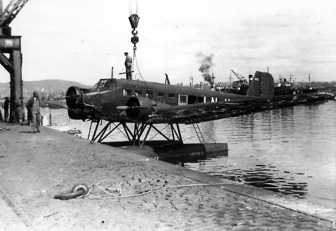 """Ett fly, Junkers Ju 52/3mg7e LN-KAB  """"Tyrihans"""", henger i heisekran. Kaidekke i forgrunnen. Røyk fra dampbåter bak."""