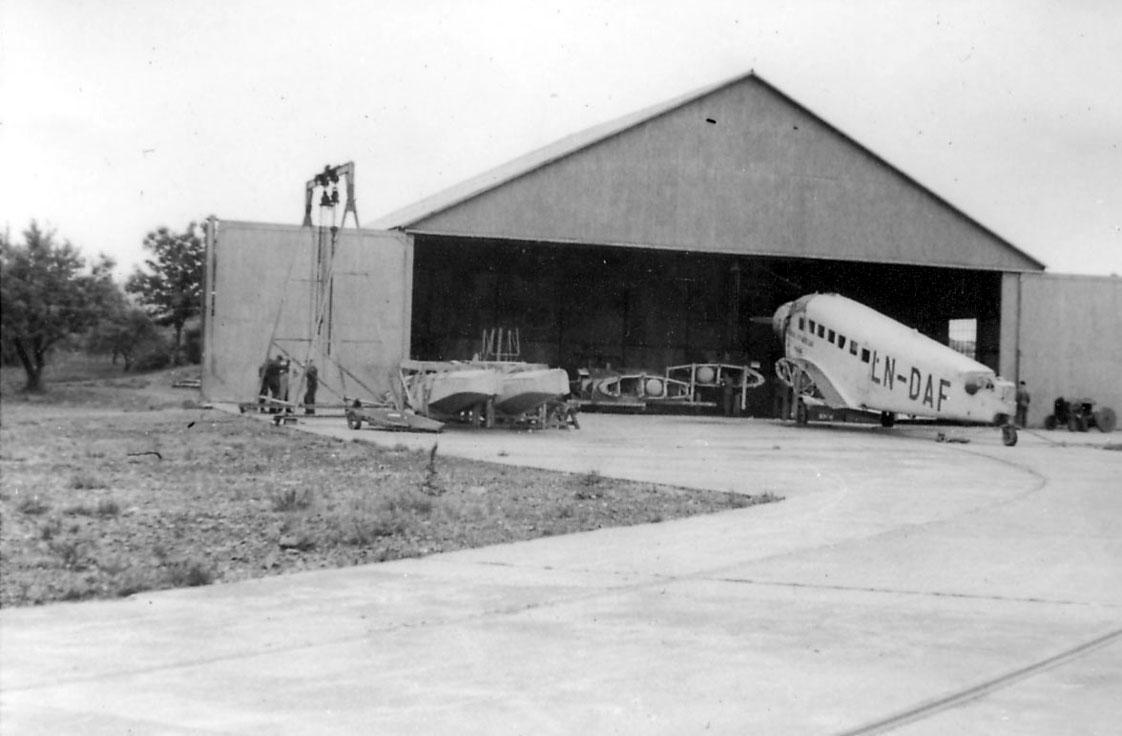 """Sjøflyhavn, ett fly på bakken, Junkers Ju 52/3mge LN-DAF, """"Najaden"""", foran en hangarbygning. Vingene og flotørene ligger ved flyet"""