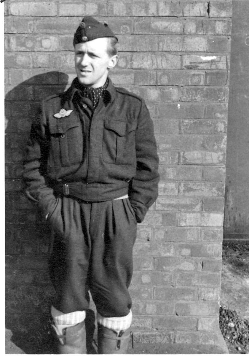 Portrett, en person i militæruniform lent mot veggen til en bygning.