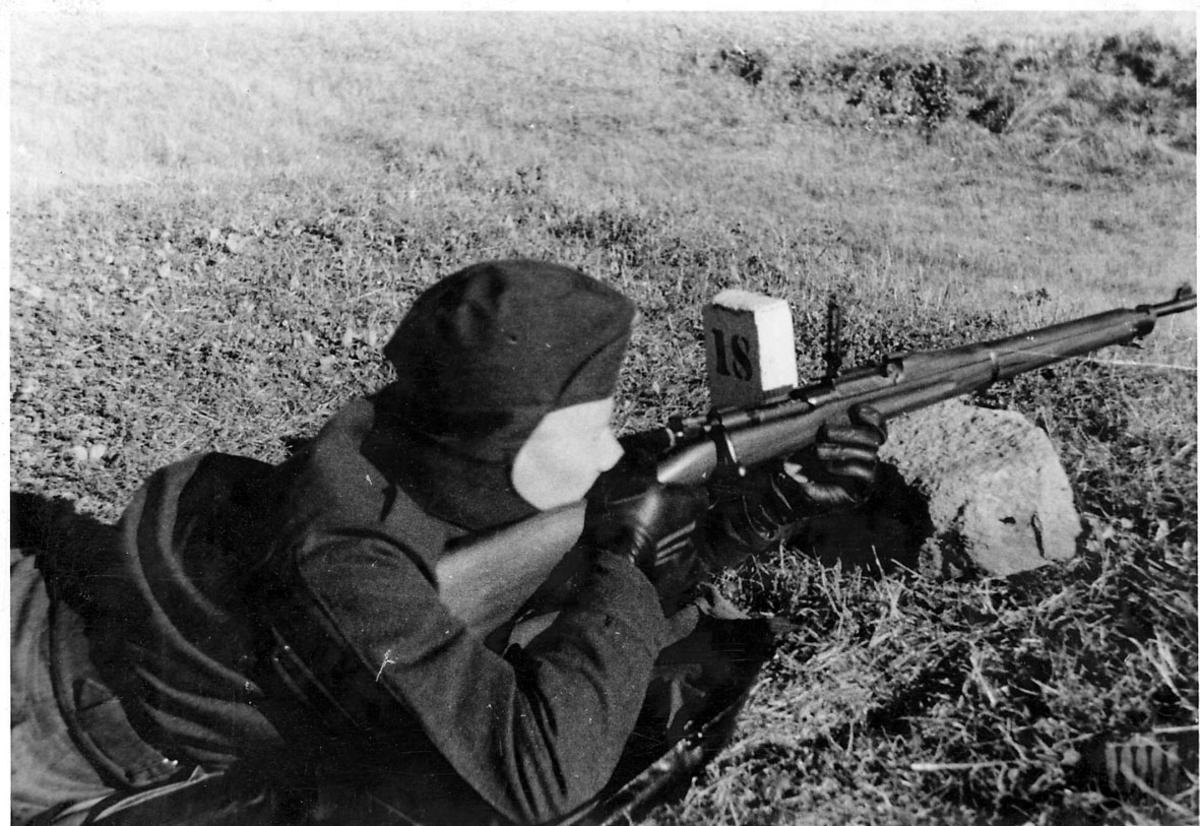 Portrett, en person ligger på bakken, med gevær. Skyteøvelse på militær skytebane.