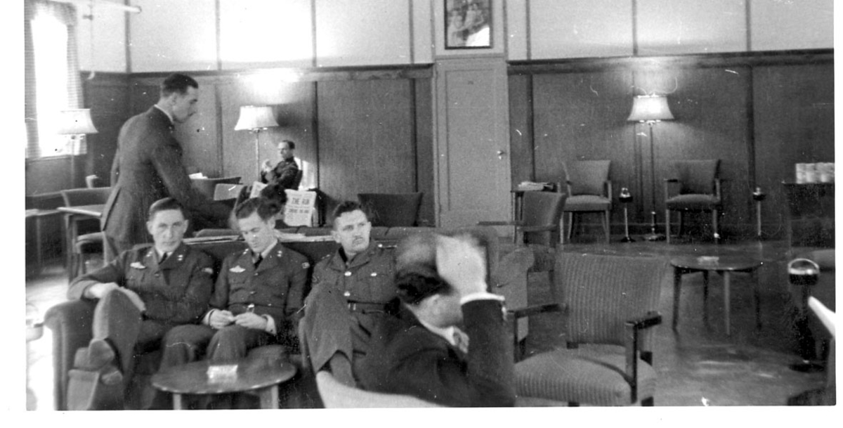 Portrett, flere personer i militæruniform, innendørs. De fleste sitter på stoler ved små bord. Fra militær mannskapsmesse?