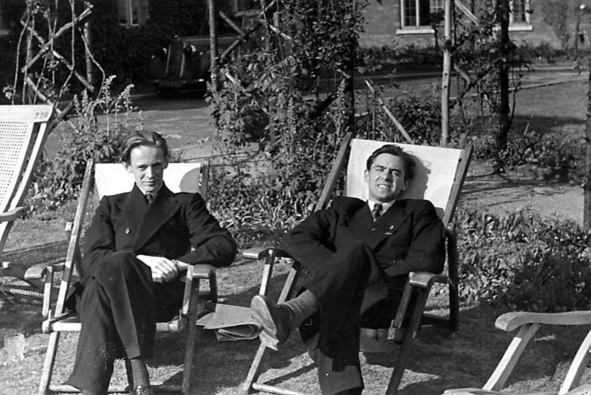 Portrett, to personer sitter i klappstoler utendørs.
