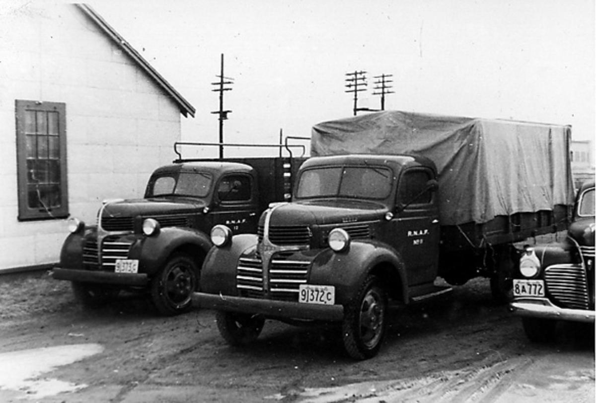 To lastebiler og litt av personbil ved siden av bygning.