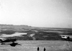 Åpen plass, ant. lufthavn, to fly på bakken. Noen personer.