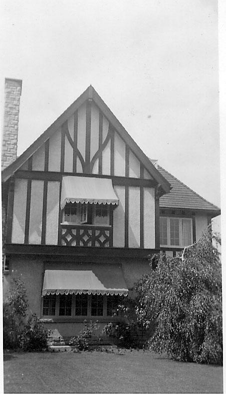 Bygning, bolig, sett utvendig. Åpen plass med prydbusker foran.
