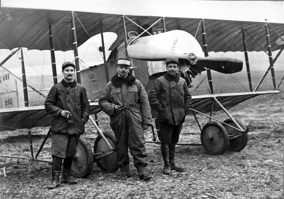 """Fly, Candron G-3. Skrått forfra. Står på bakken. 3 personer - flygere - foran flyet. """"PEACE"""" skrevet på motordeksel."""