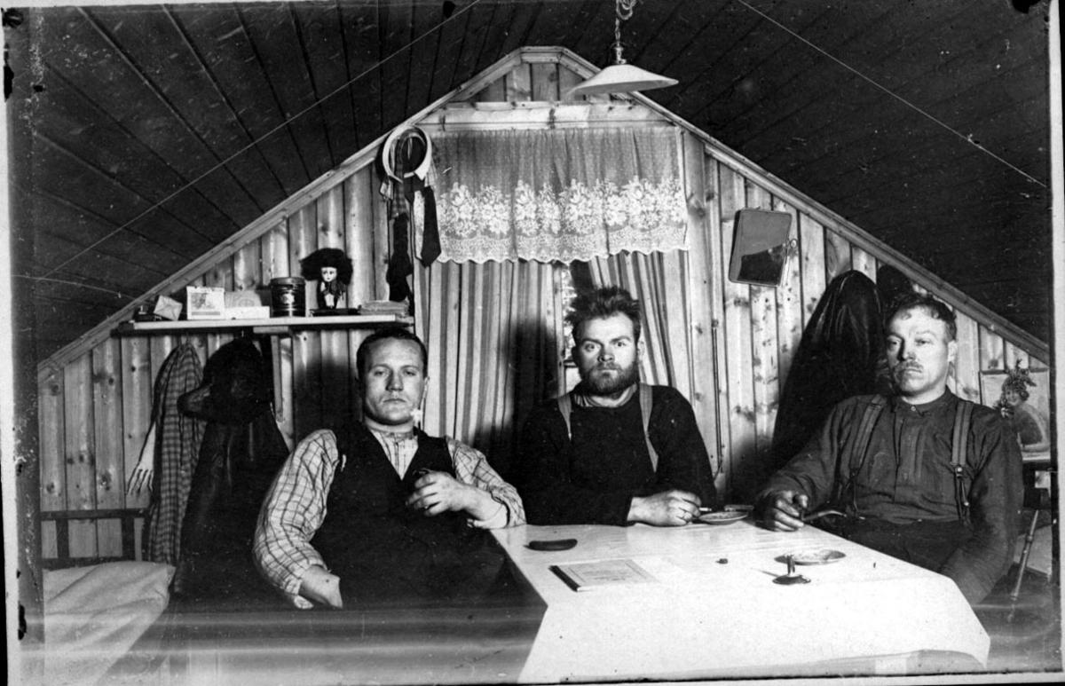 Tre personer, tatt innendørs. Sitter ved et bord. Vindu med gardiner, hylle og klær på veggen bak.