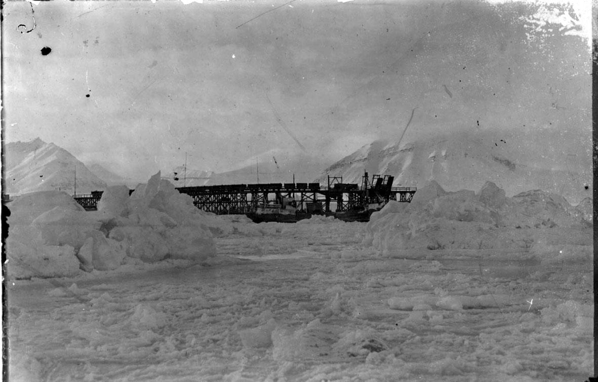 """Kai med flere jernbanevogner. Fartøyet """"Hobby"""" ligger ved kaia. Ismasser i forgrunnen, snø."""