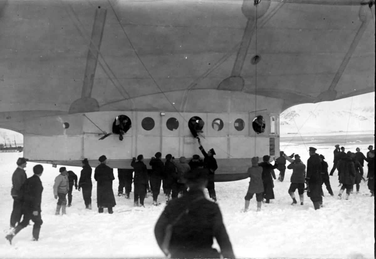 """Luftskipet """"Norge"""", undersiden med gondolen, personer i vinduene. Mange personer ved luftskipet. Fartøy ved kai, i bakgrunnen, fjorden og fjell. Snø på bakken"""