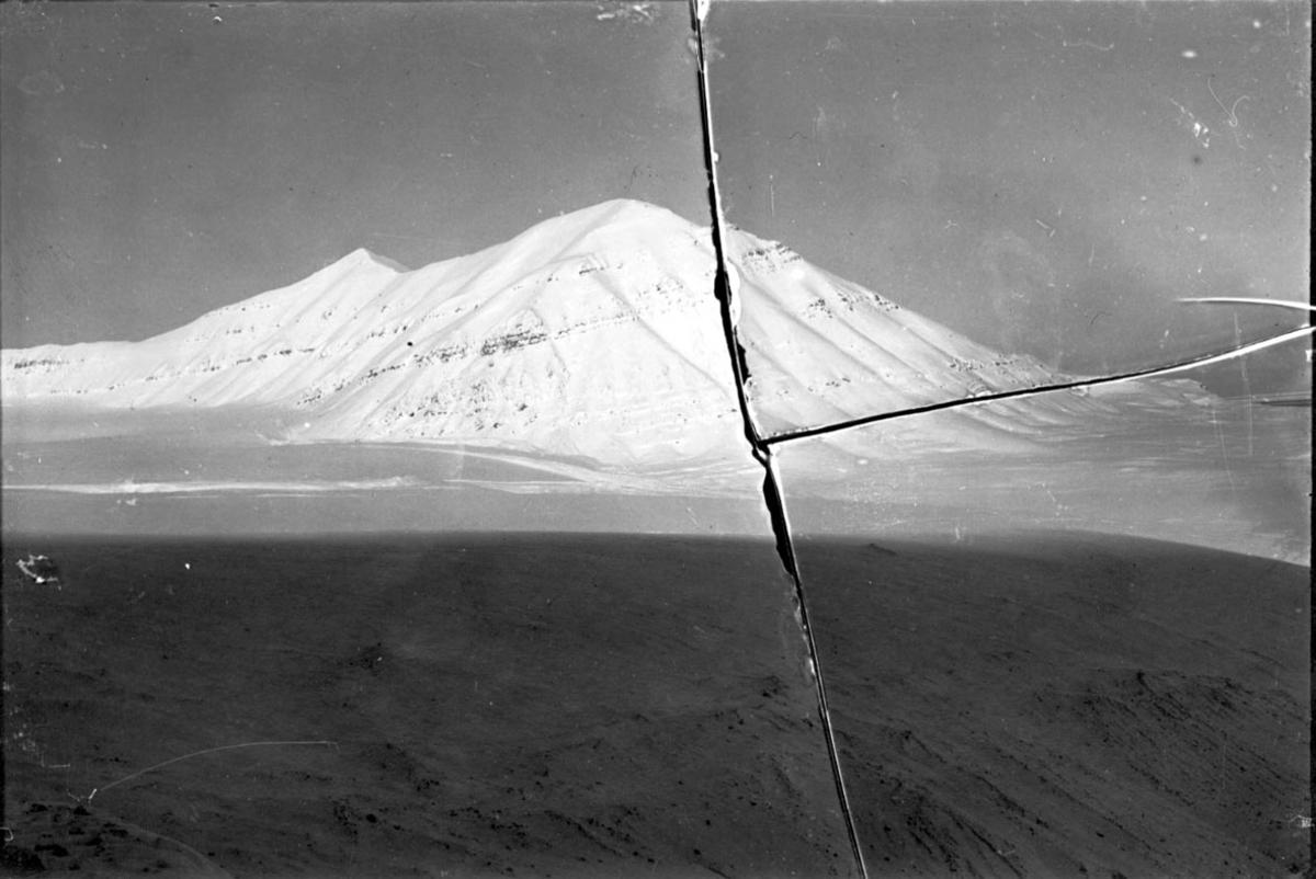 Landskapsmotiv fra Svalbard. Fjell bak. Snø på bakken.