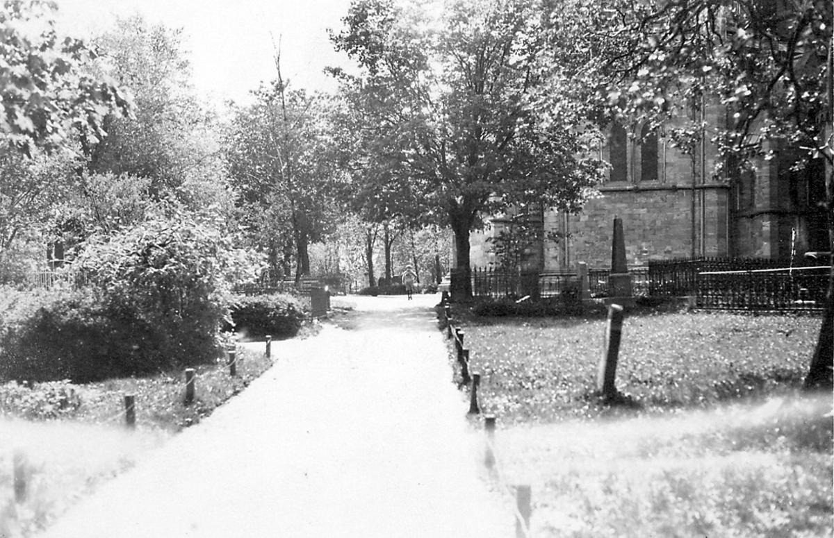 Kirkegård, vei i forgrunnen. Litt av kirka sees t.h. Flere trær. Området ved Nidarosdomen.