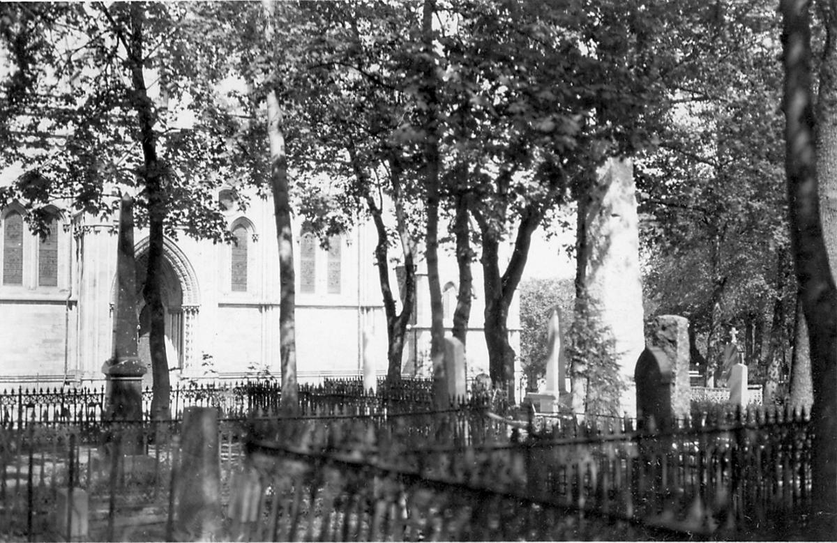 Kirkegård i forgrunnen, litt av kirke, Nidarosdomen, sees bak.