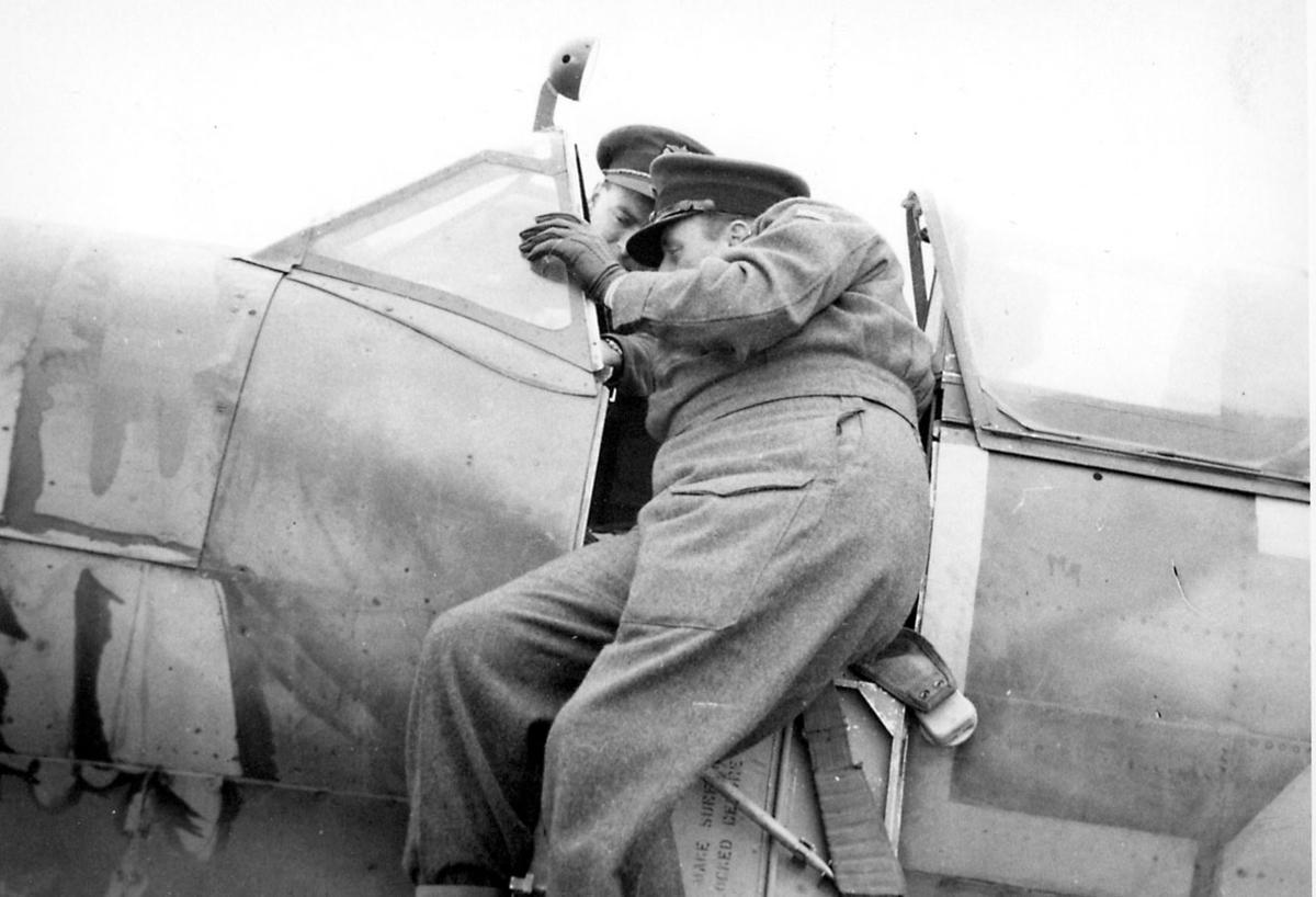2 personer i militæruniform. Kronprins Olav og en annen, studerer cockpiten på et fly. Flyet er en Spifire