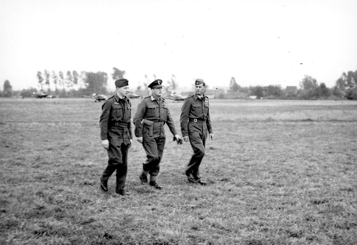 3 personer i militæruniform. Kronprins Olav sammen med 2 andre,  på en åpen plass. Noen fly i bakgrunnen.